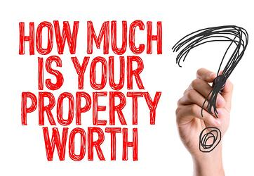 Hand with marker writing How Much Is Your Property Worth?
