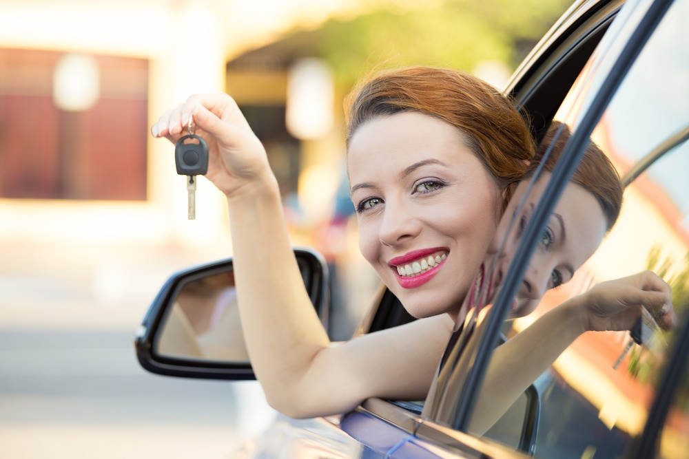 Closeup portrait happy, smiling, young attractive woman, buyer sitting in her new blue car showing keys isolated outside dealer, dealership lot, office. Personal transportation, auto purchase concept.jpeg
