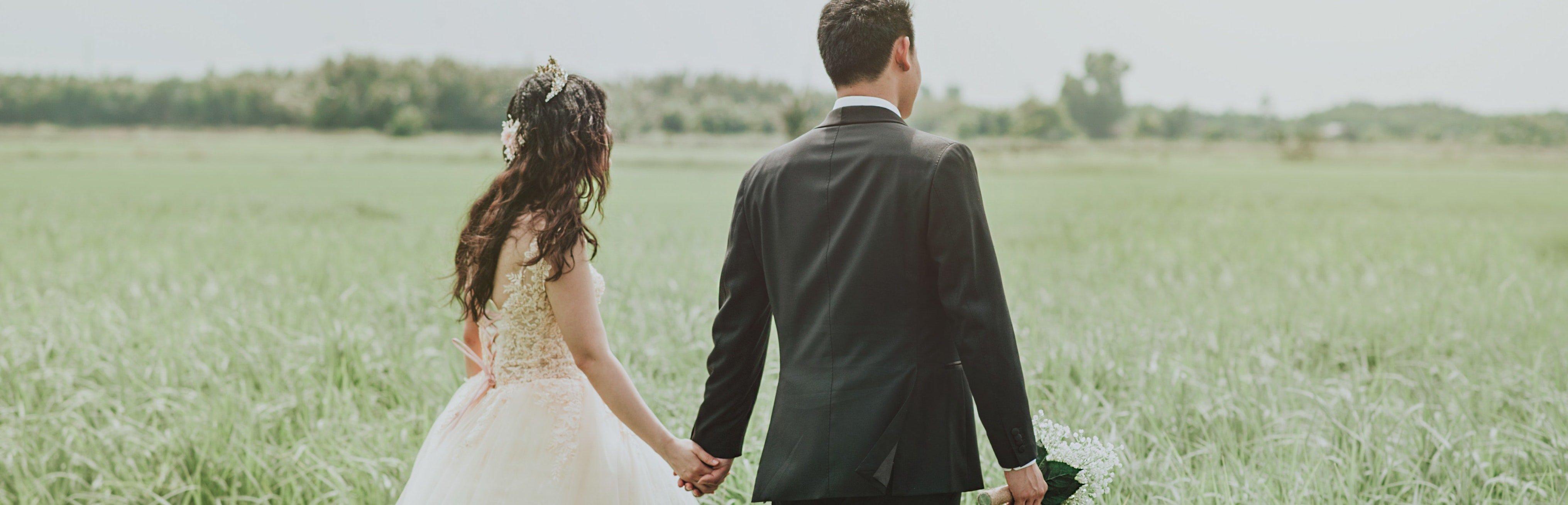 Married couple walking in field.