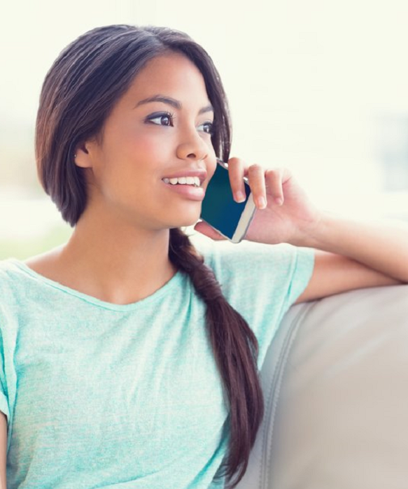 Cheerful girl sitting on sofa making a phone call at home in the living room trim