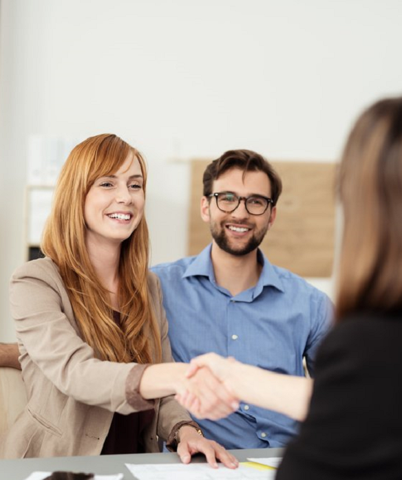 Happy young couple meeting with a broker in her office leaning over the desk to shake hands, view from behind the female agent trim