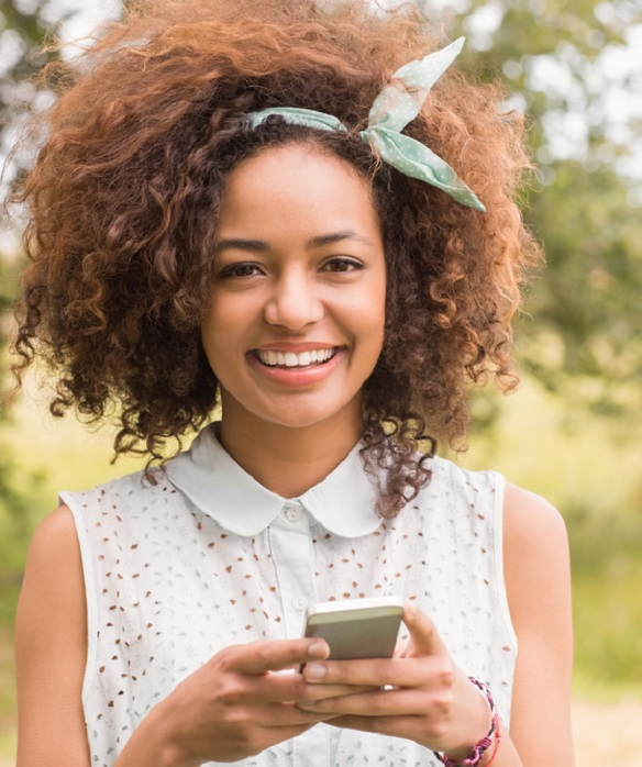 Happy young woman using smartphone on a sunny day trim