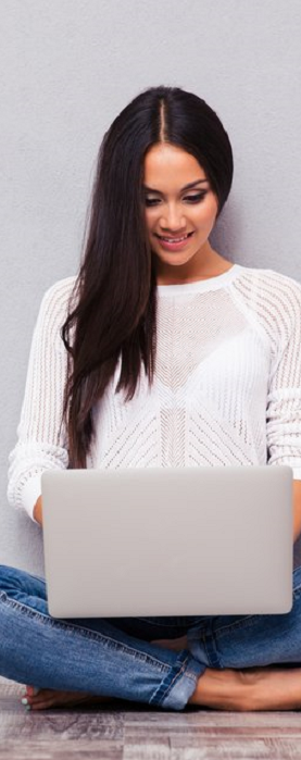 Portrait of a happy casual woman sitting on the floor with laptop on gray background trim