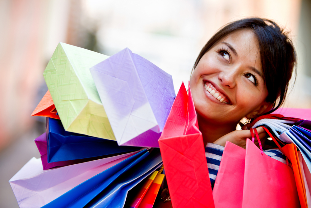 Happy shopping woman with bags and smiling