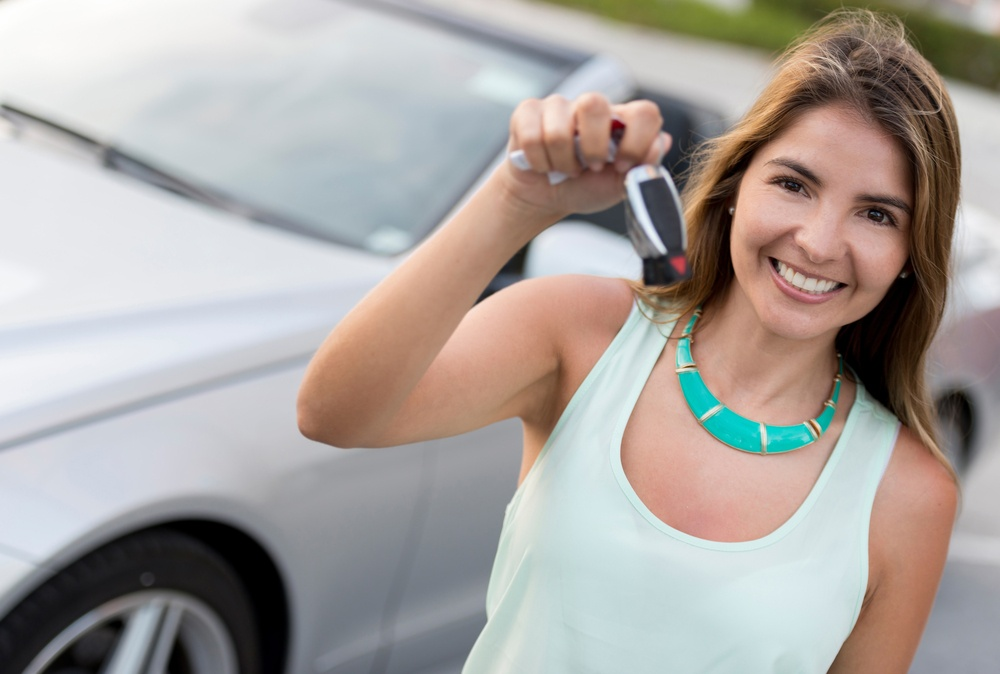 Woman holding car keys and looking very happy
