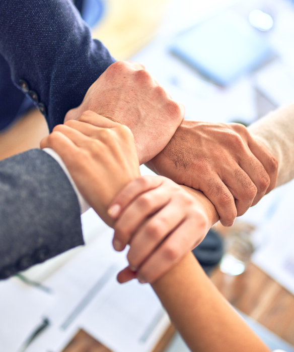hands in a huddle representing a business management team
