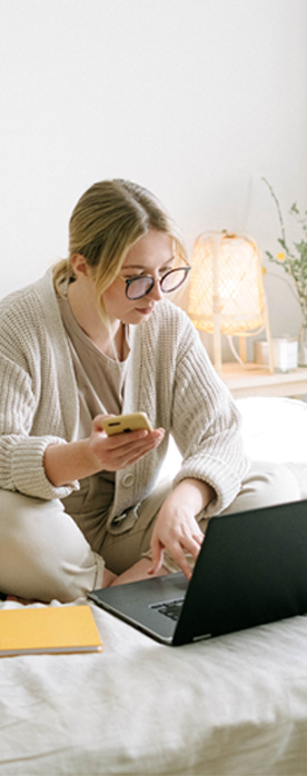 woman completing her online application while sitting on her bed
