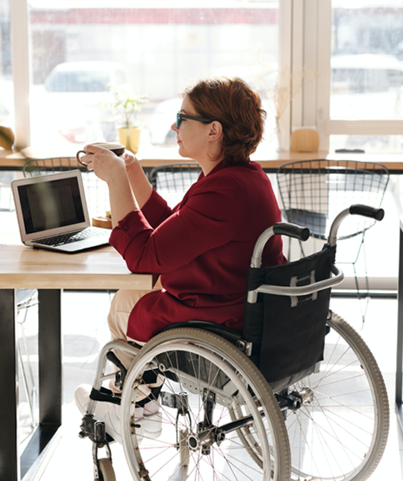 america's credit union makes eStatements easy image of woman in wheelchair in coffeeshop on laptop